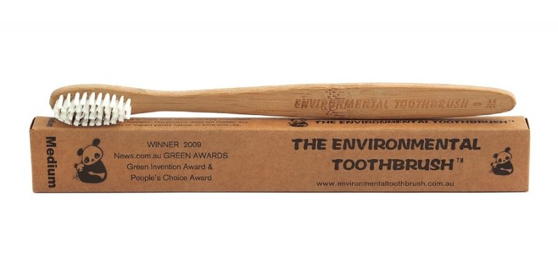 bamboo toothbrush sitting on its 100% recyclable packaging